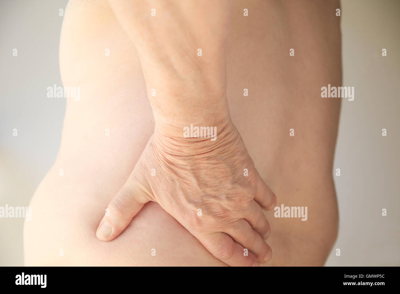A shirtless man has his hand on his sore back. - Stock Image