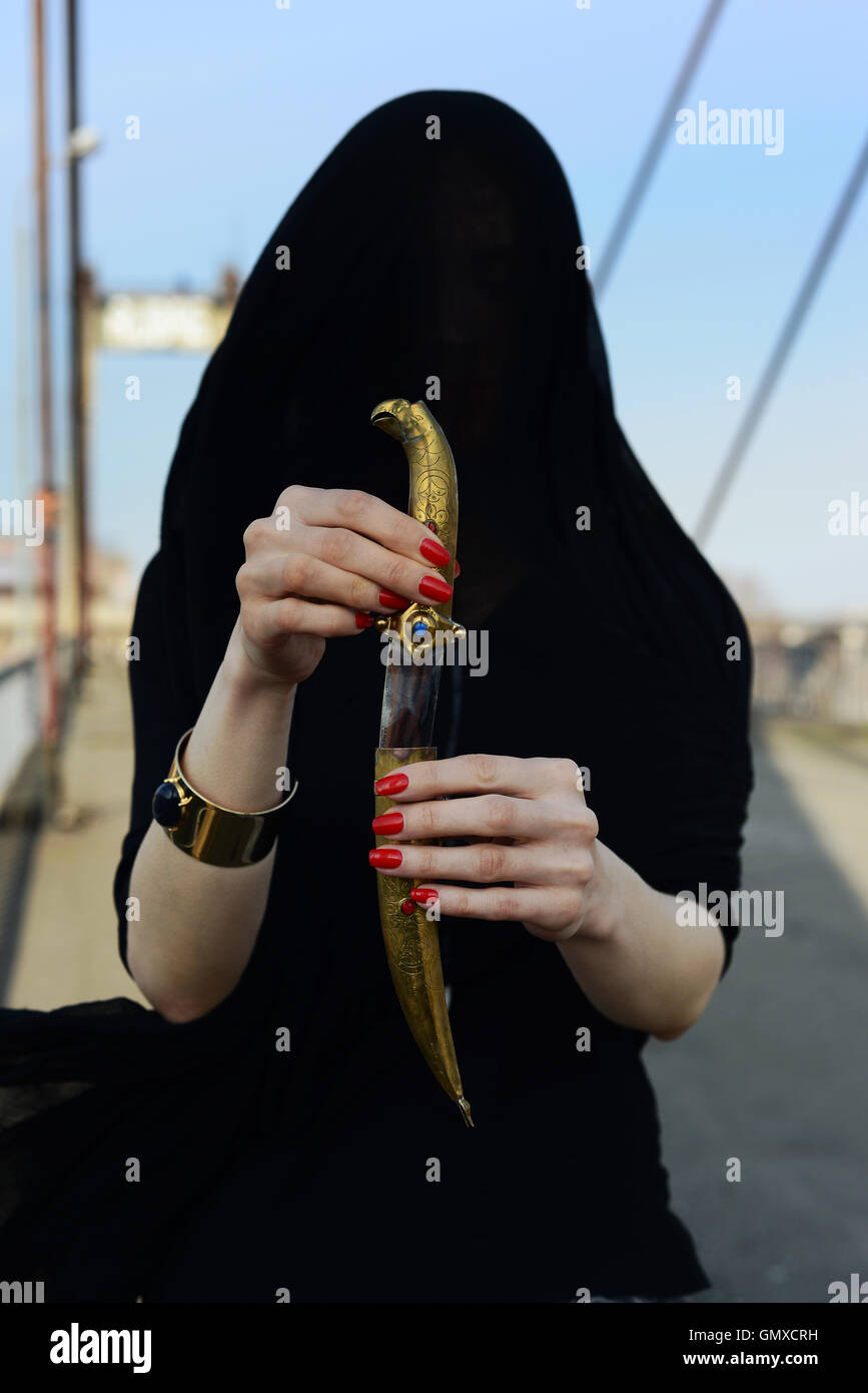 Girl in black with an oriental dagger - Stock Image