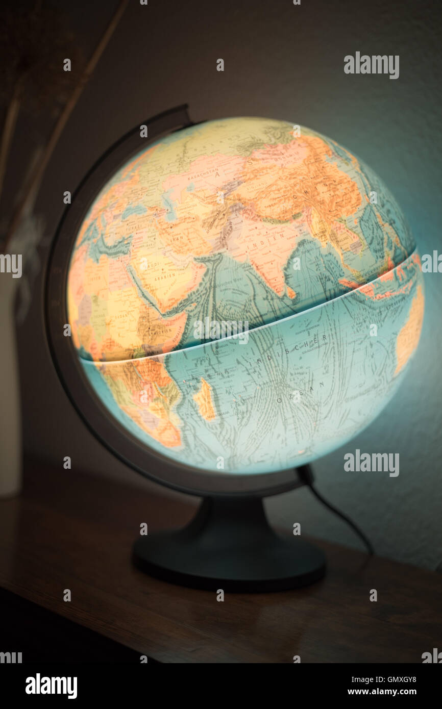 Illuminated Globe on shelf.  Beleuchteter Globus. - Stock Image