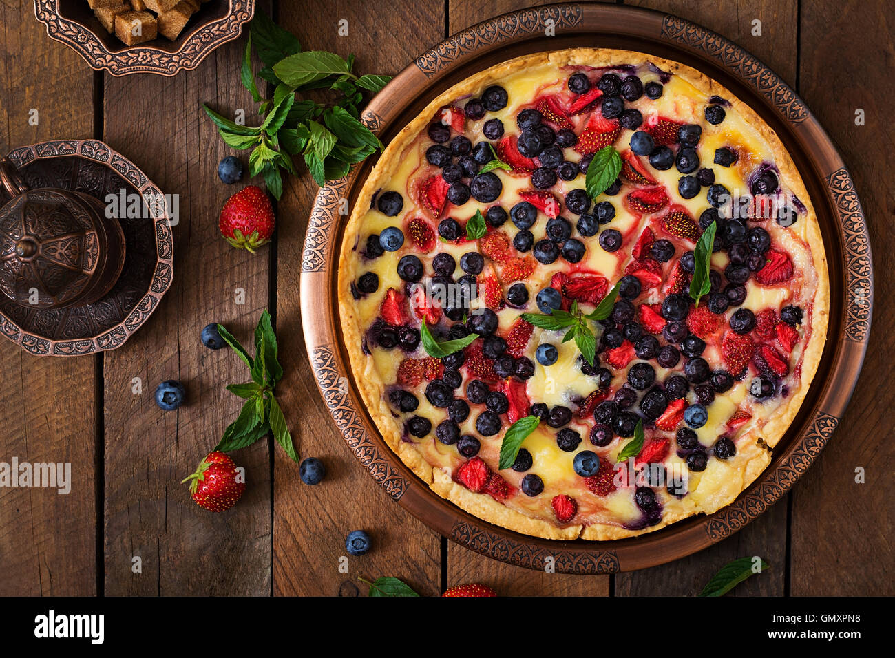 French tart (flan) with berries and custard. Top view - Stock Image