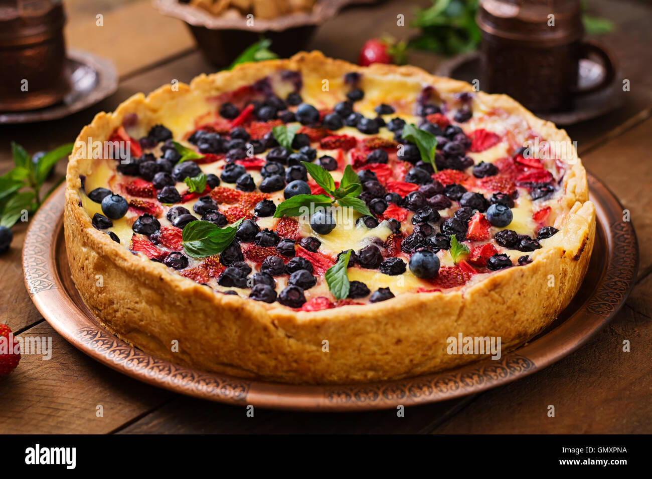 French tart (flan) with berries and custard. - Stock Image