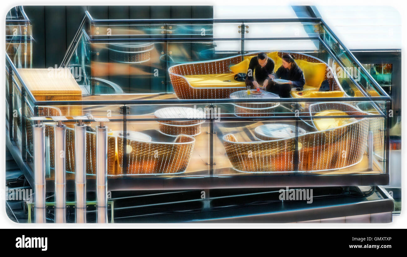 Couple romantically dining on a rooftop bar - Stock Image