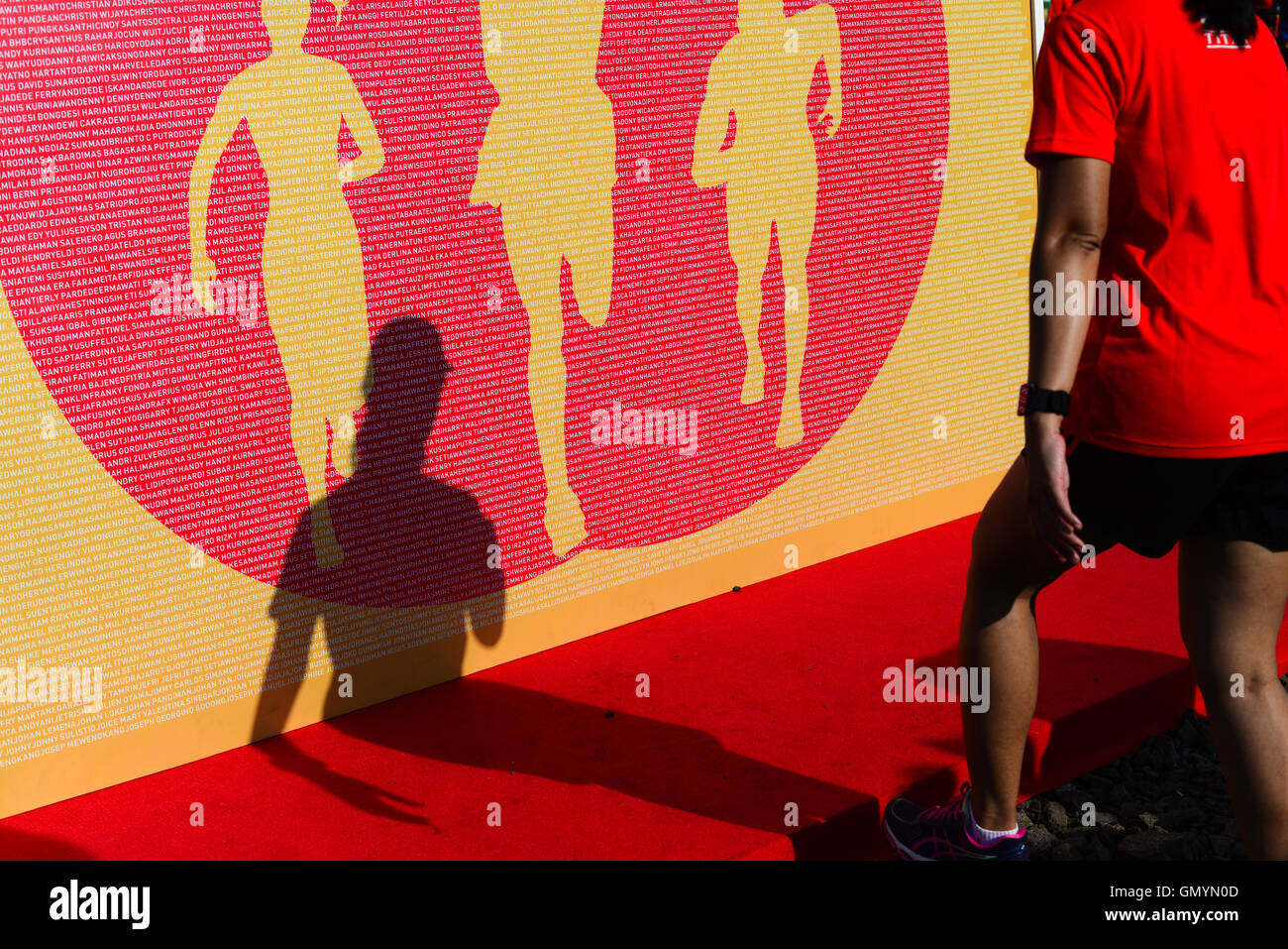 Shadow of a woman and giant poster illustrating runners in competition. - Stock Image