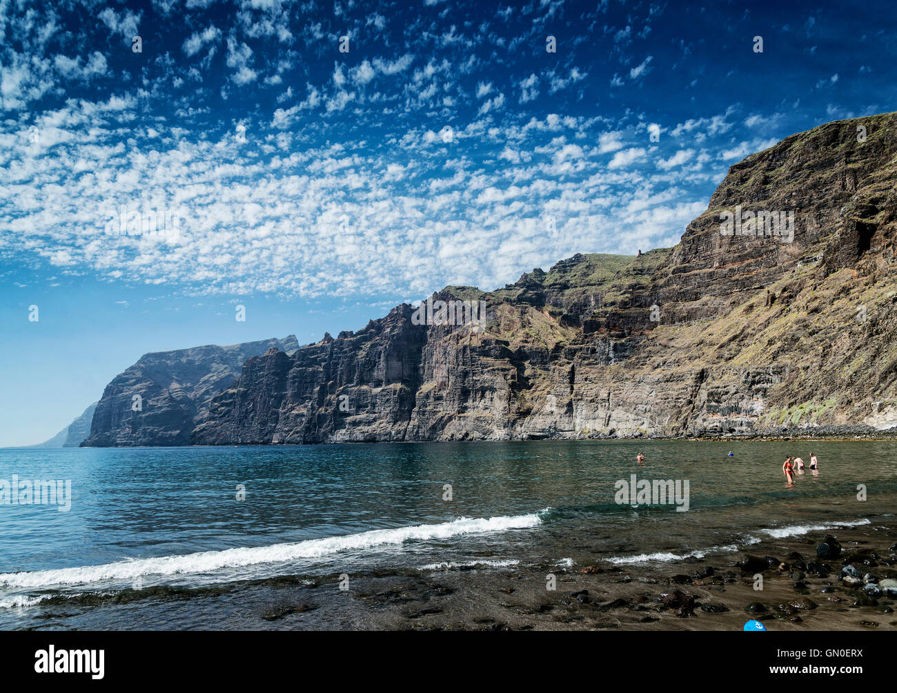 tourists bathing at los gigantes volcanic black sand beach by famous natural cliffs landmark in south tenerife island - Stock Image