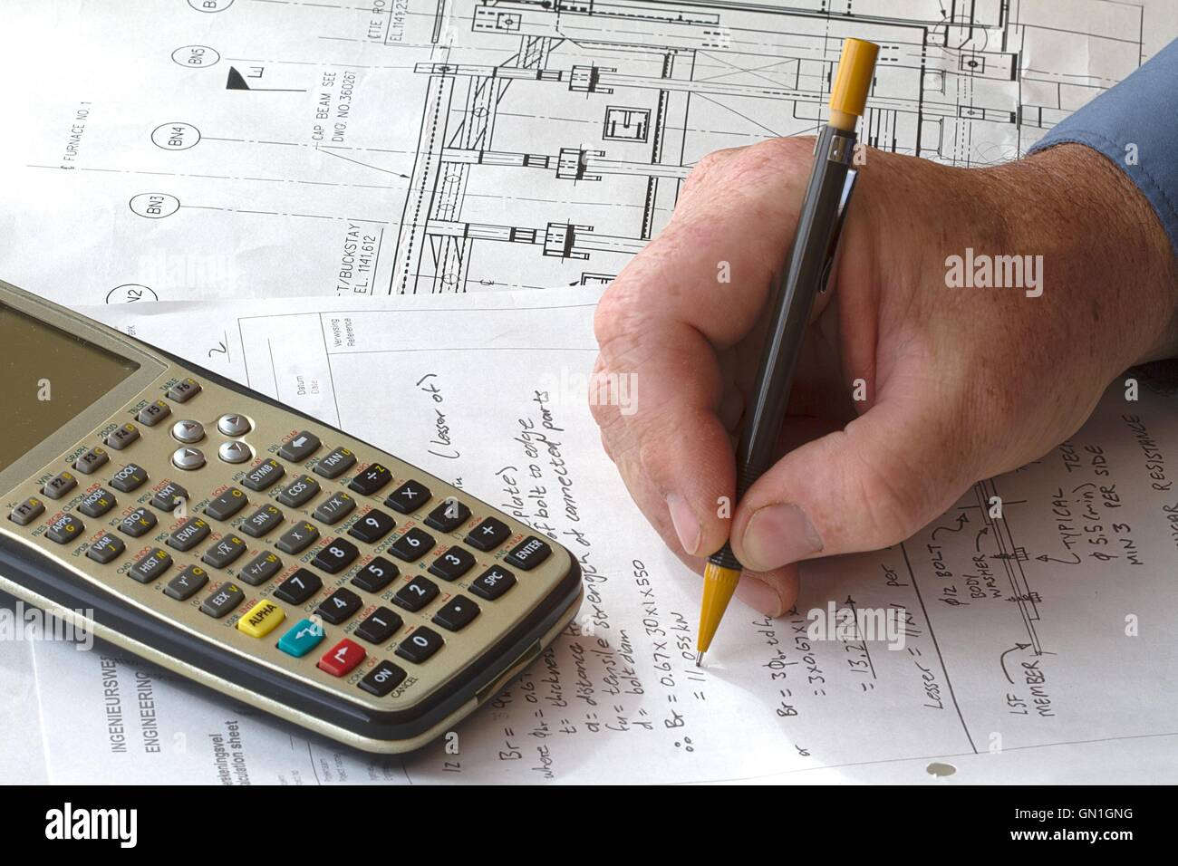 Engineer doing hand calculations on a calculation sheet, with a calculator on the side - Stock Image