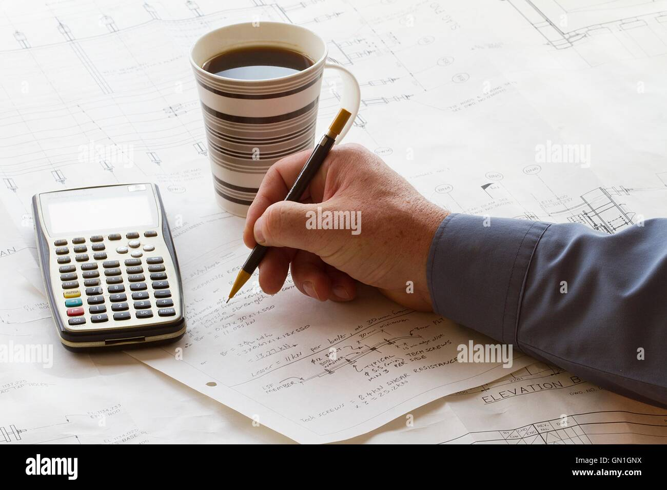 Engineer doing hand calculations on a calculation sheet, with a calculator and cup of coffee - Stock Image