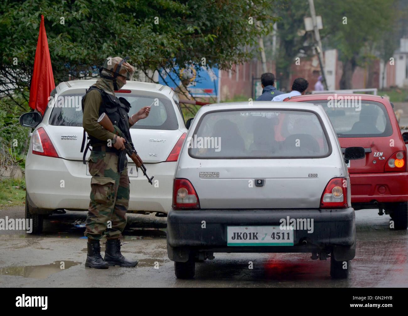 Srinagar, Kashmir. 27th Aug, 2016. An Indian army man cheks the identity card of local inhabitant in Srinagar the - Stock Image