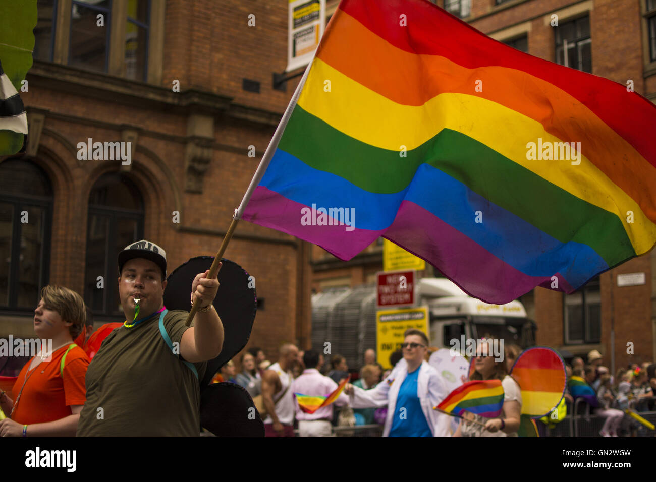 Manchester, UK. 27th August, 2016. Manchester Pride Parade. Man wearing wings waves gay pride flag Credit:  Tom Stock Photo