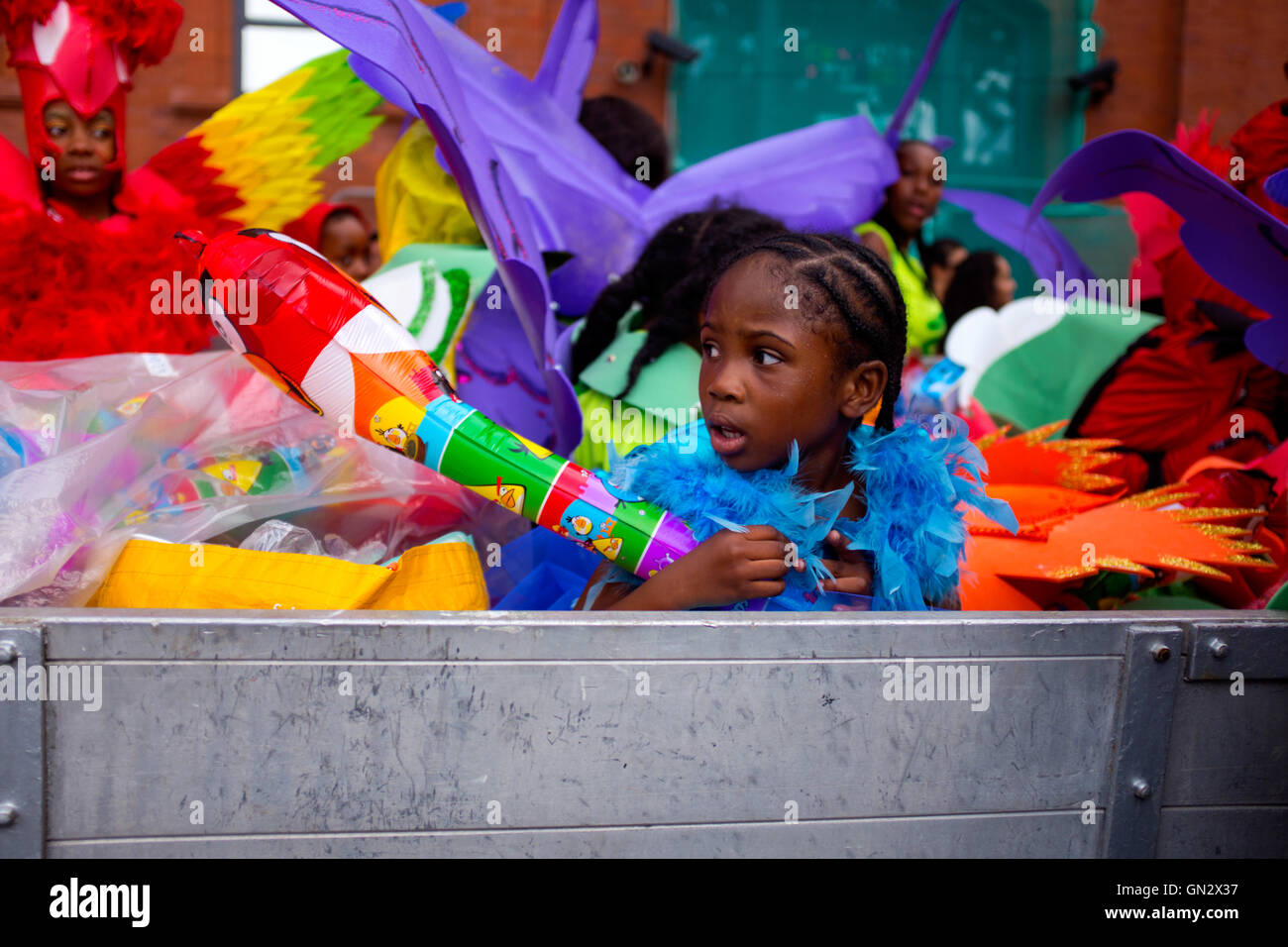 Young girl reveler sits in a truck at the 50th Notting Hill Carnival, London, 2016. Credit:  Wayne Tippetts/Alamy - Stock Image