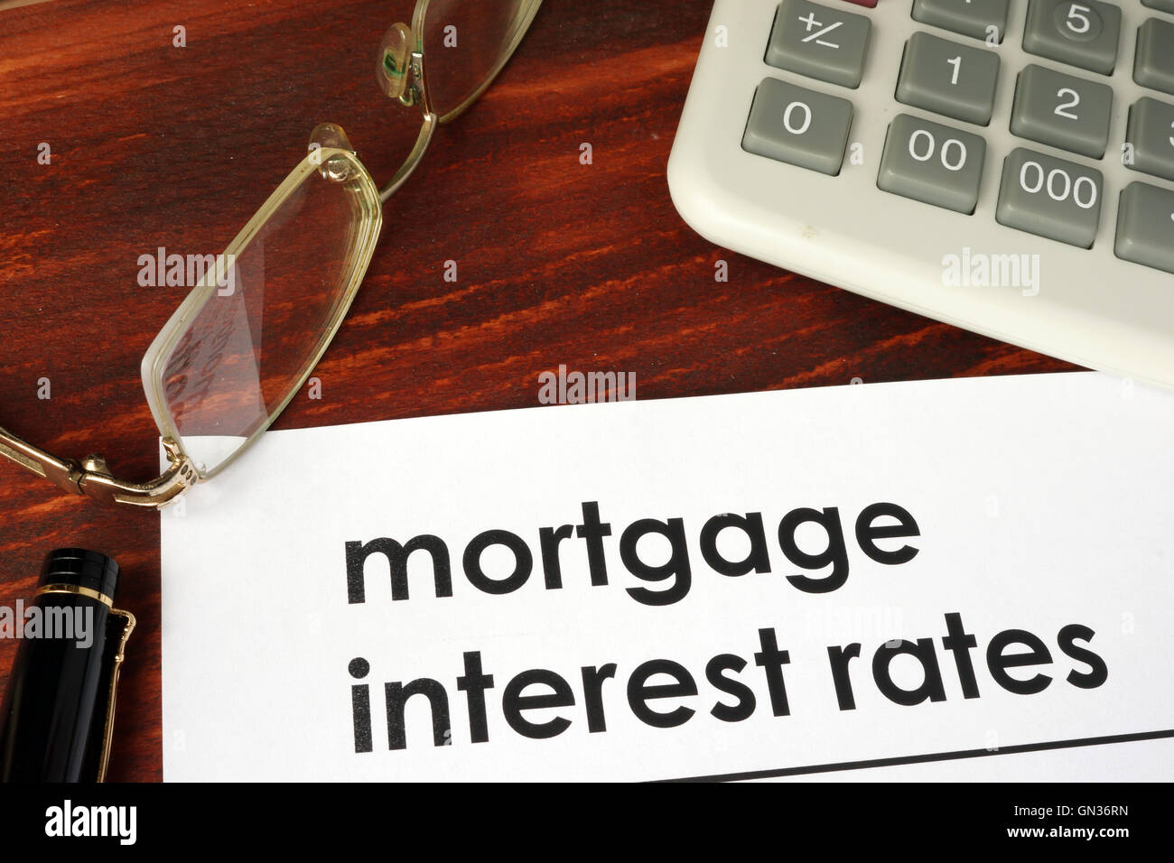 Paper with words mortgage interest rates on a wooden background. - Stock Image