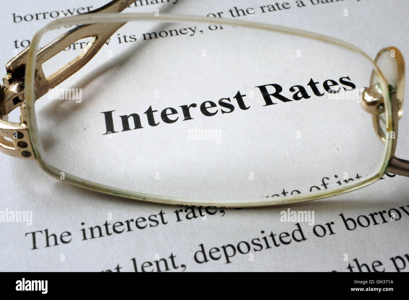 Page of paper with words interest rates and glasses. - Stock Image