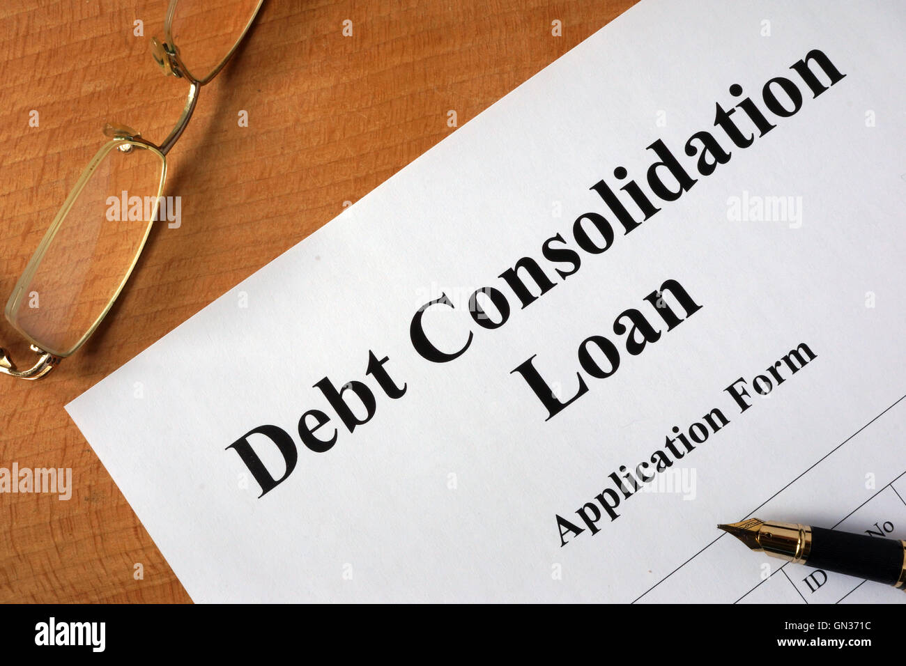 Debt consolidation loan form on a wooden table. - Stock Image