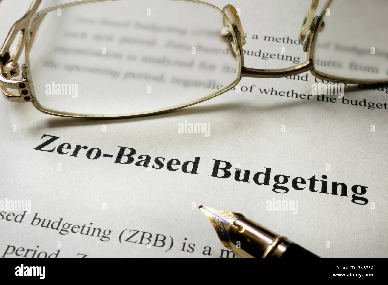 Sign Zero-Based Budgeting - ZBB on a paper and glasses. - Stock Image