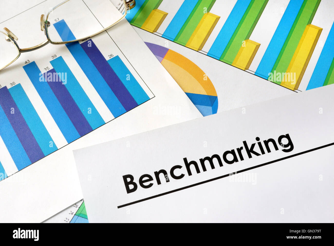 Paper with words Benchmarking and charts. - Stock Image
