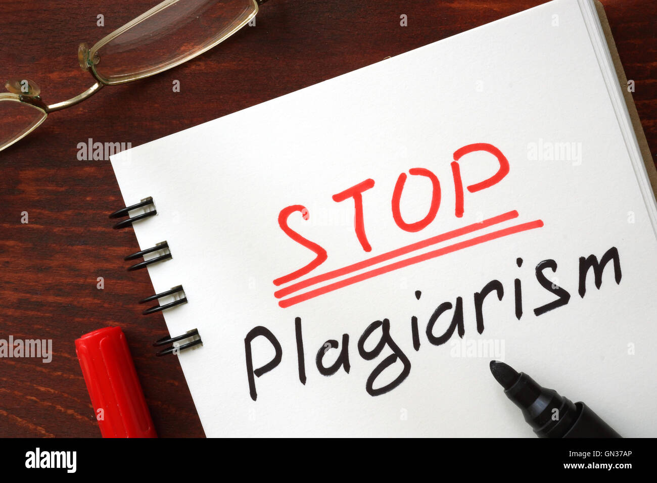 Stop plagiarism sign written in a notepad. - Stock Image