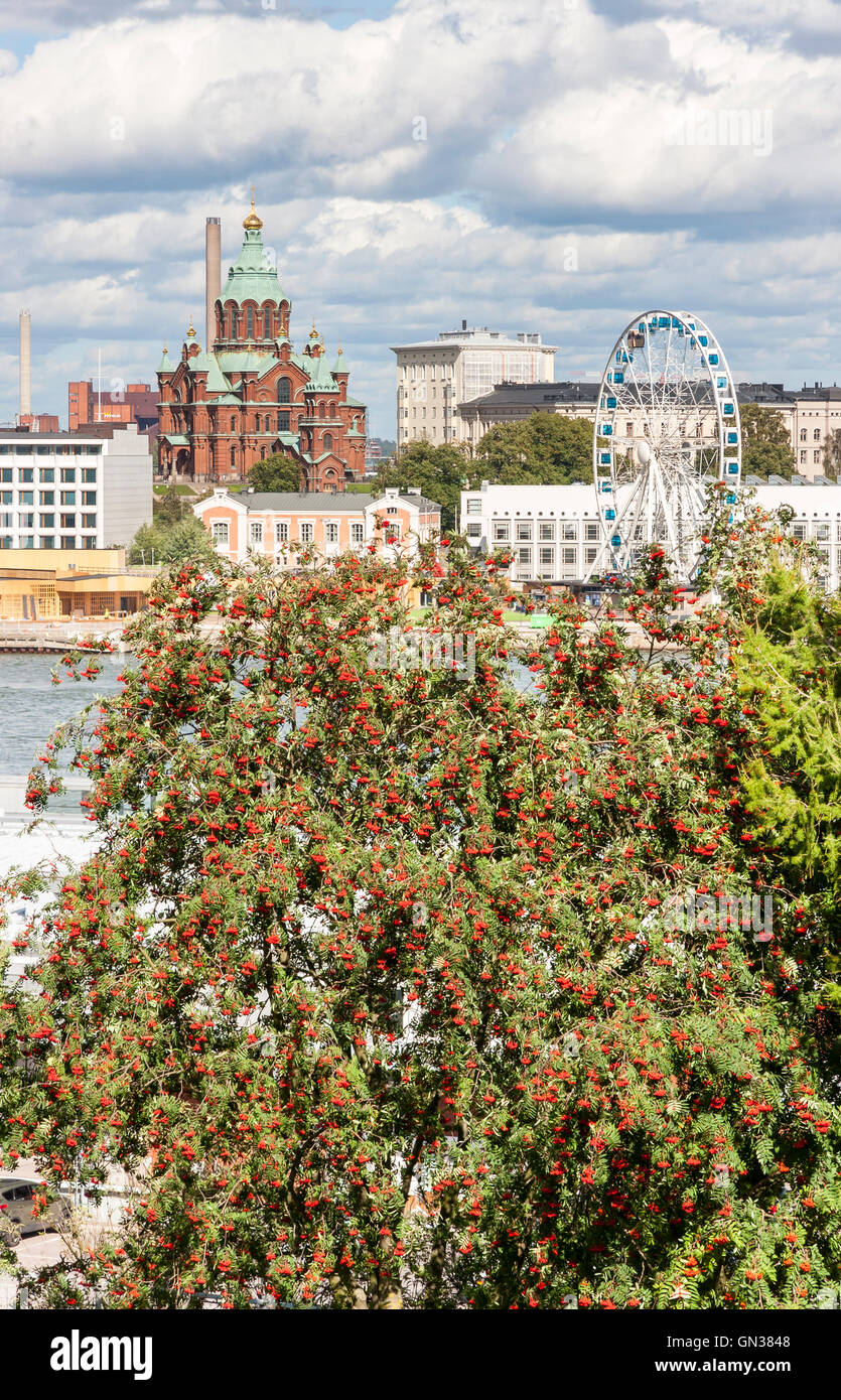 Church and a ferries wheel behind rowan tree in Helsinki, Finland - Stock Image