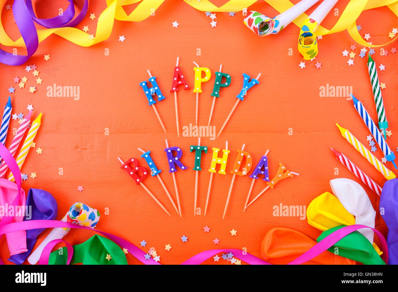 Happy Birthday Background With Decorated Borders Party Decorations On A Bright Orange Wood Table Candle
