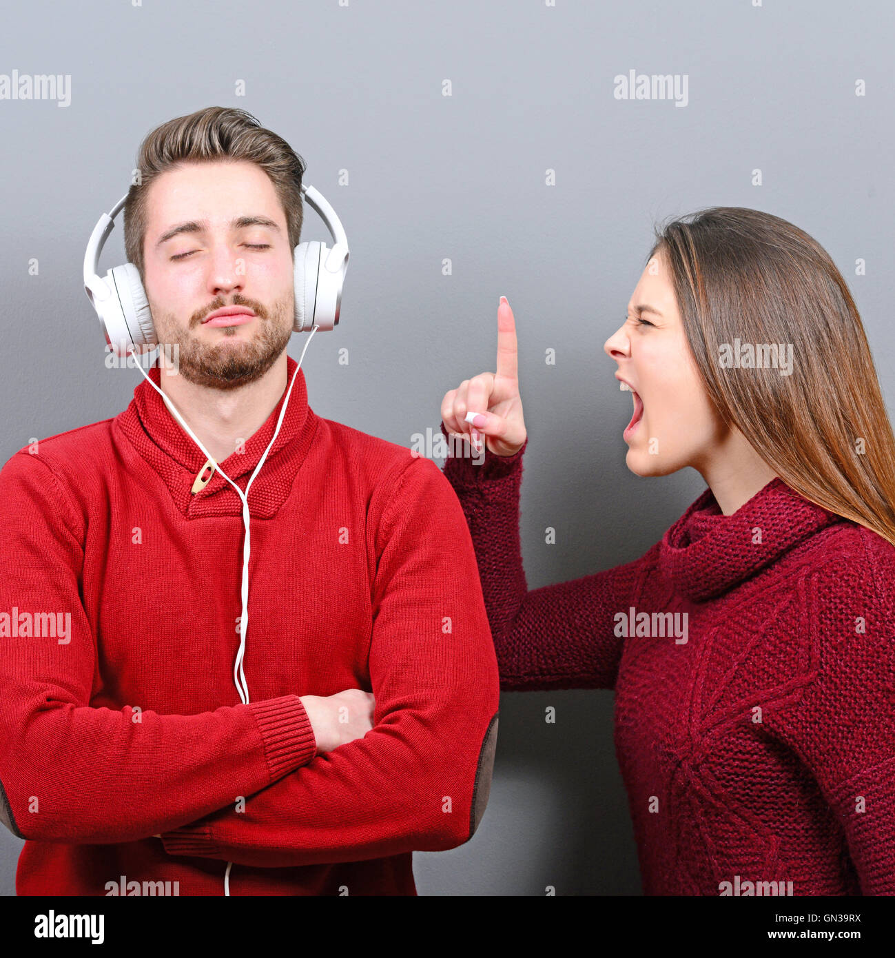 Man listening to music and doesnt care about her screaming at him - Stock Image