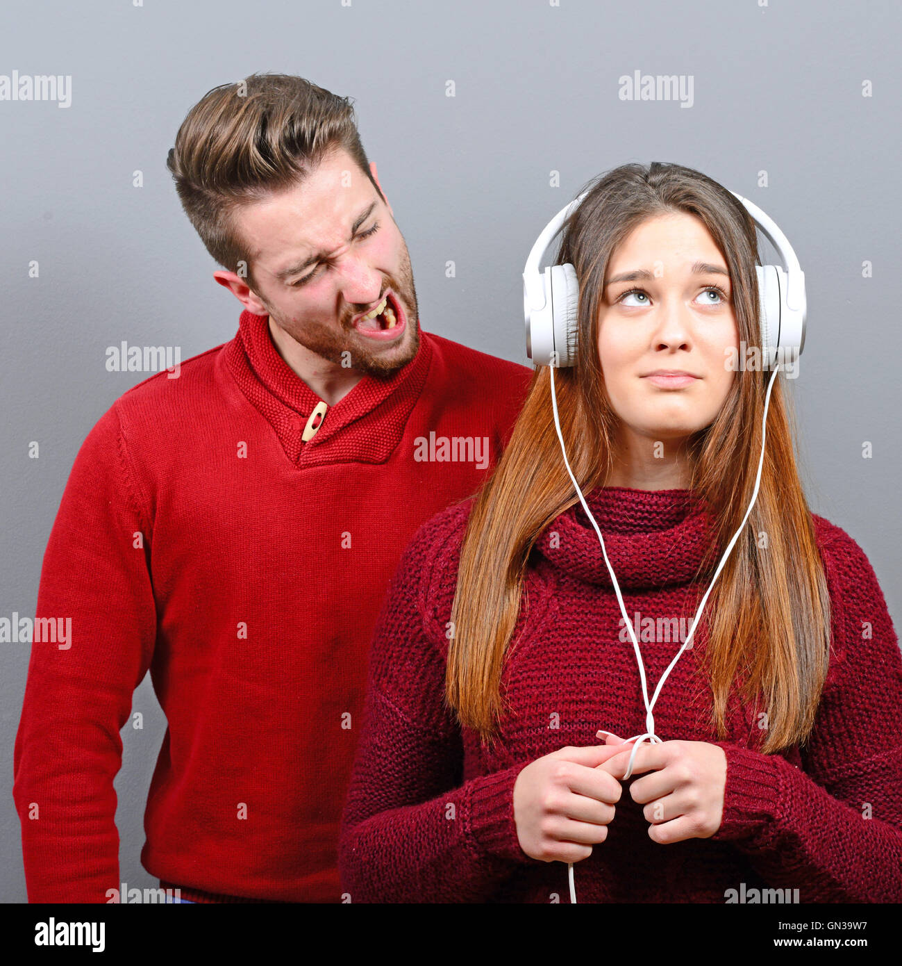 Woman listening to music and doesnt care about him screaming at her - Stock Image