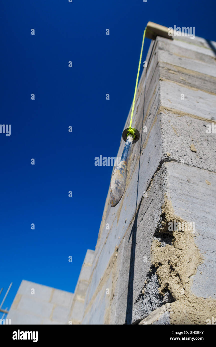 Builder's plumb line hanging against exterior corner wall of house build in progress. Stock Photo