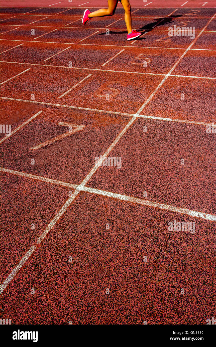 Legs of a woman running on an athletics track - Stock Image