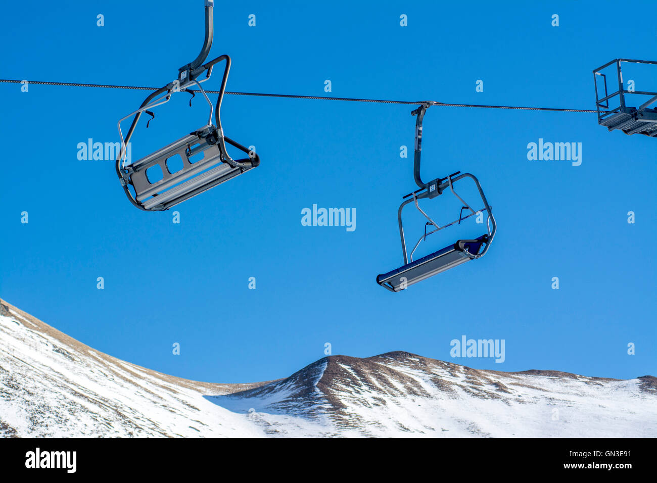 Chairlift and lack of snow in a ski resort in France - Stock Image