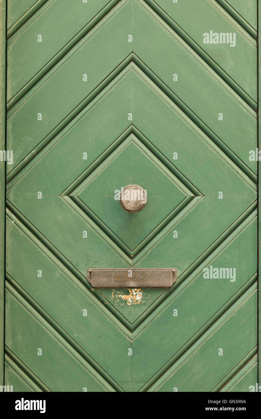 A green painted wooden door with diamond pattern, round door knob and mail slit. - Stock Image