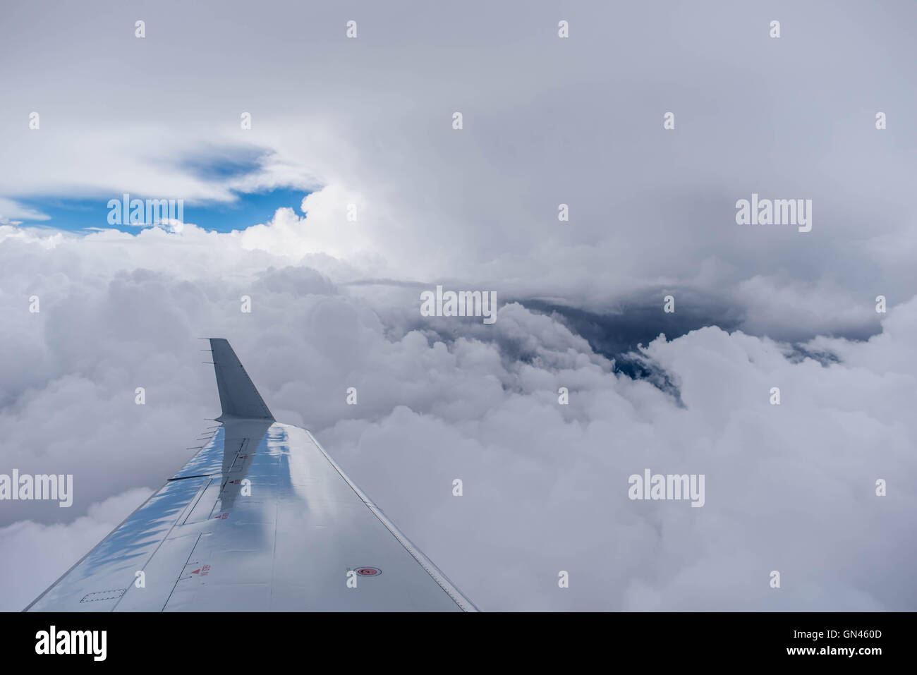 Airplane Wing Tip against a Cloudy Sky, with a hint of blue - Stock Image