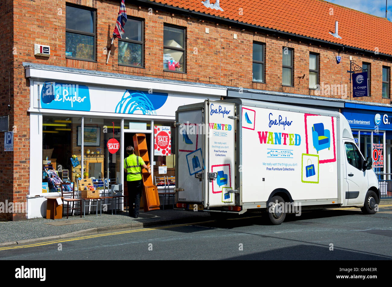 Delivery van parked outside Sue Ryder charity shop, England UK - Stock Image