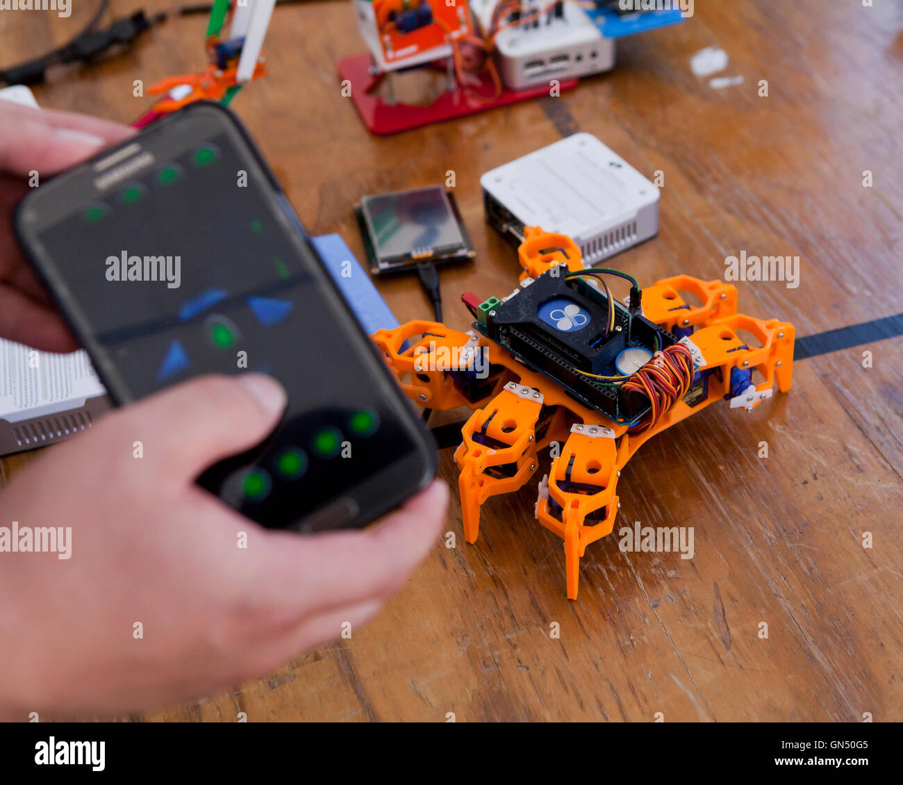 Man controlling toy robot with mobile phone ap via bluethooth - USA - Stock Image