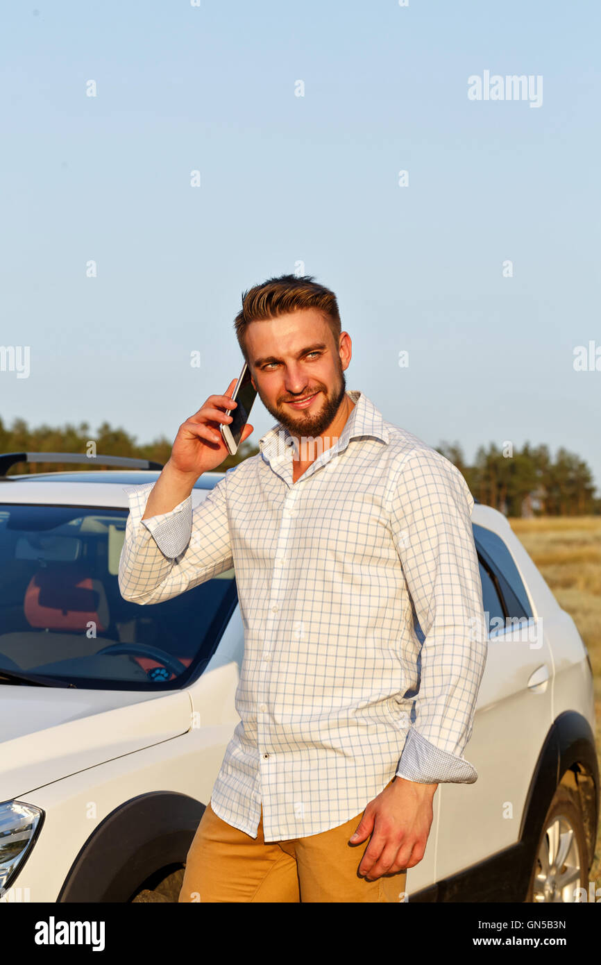 Young handsome man standing in front of the car. A man talking on a smartphone and smiles. Always connected. - Stock Image