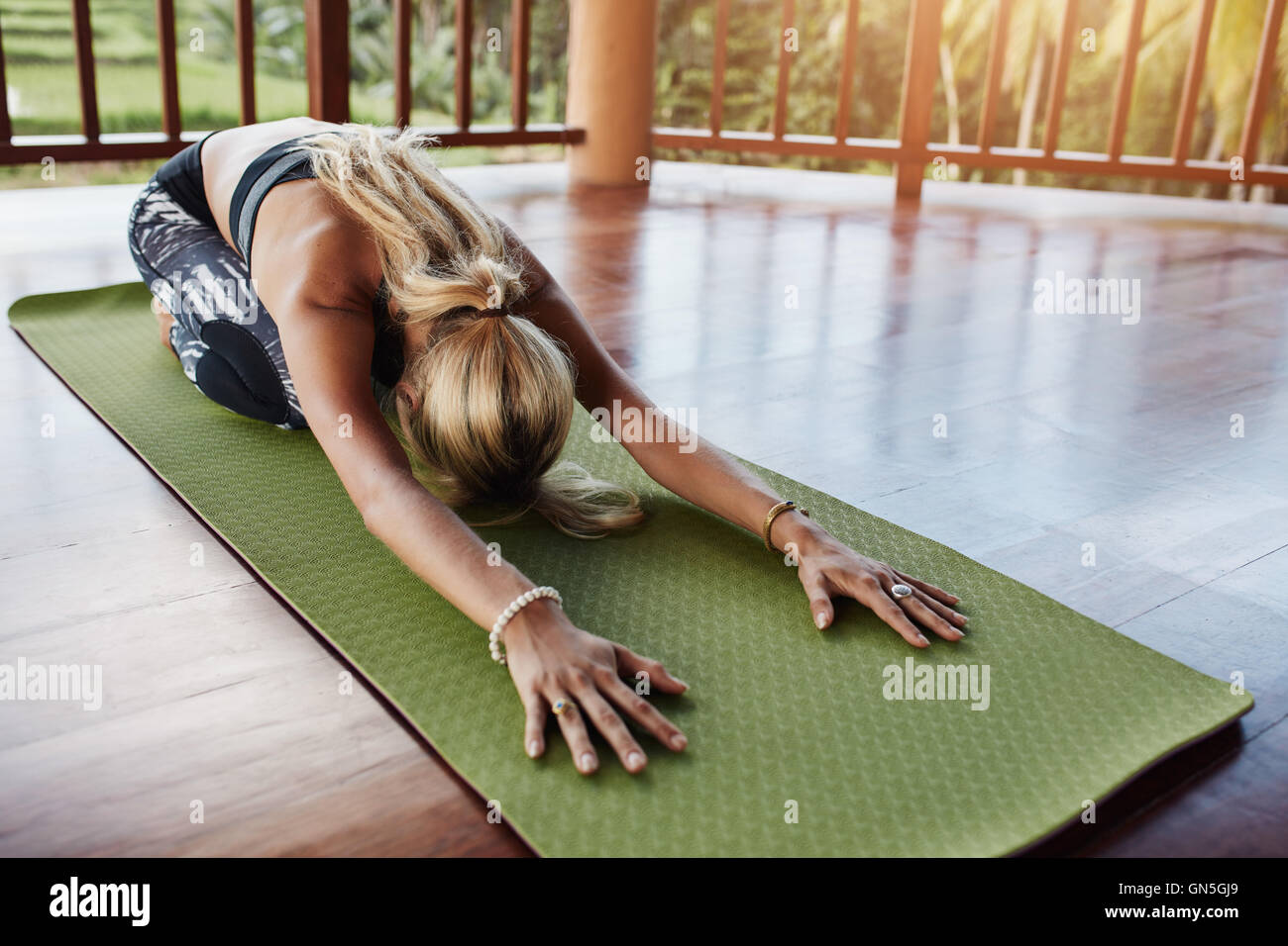 Young woman doing stretching workout on fitness mat. Female performing yoga on exercise mat at gym. Child Pose, Stock Photo