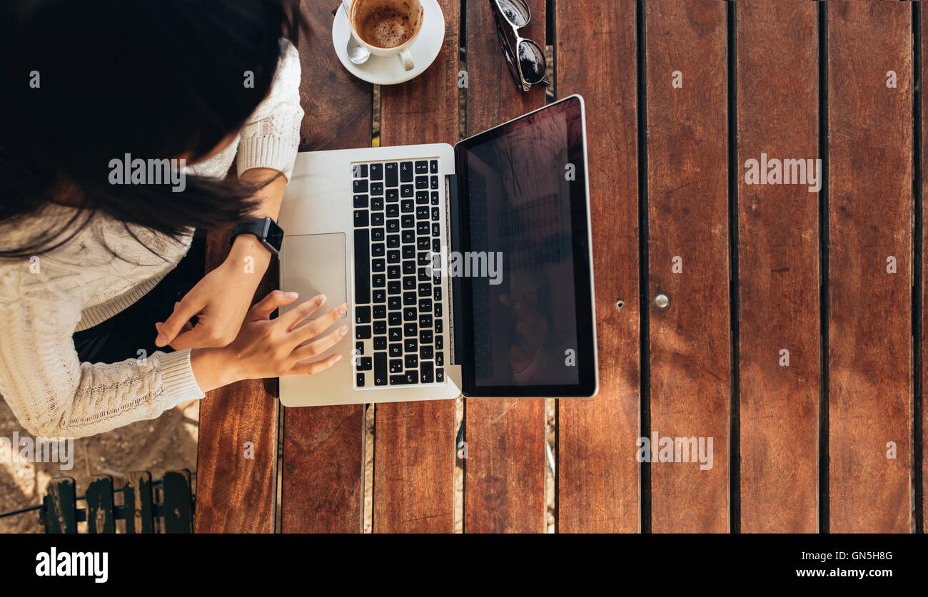 Overhead view of young woman working on her laptop at a cafe. Top view shot of female sitting at a table with a - Stock Image