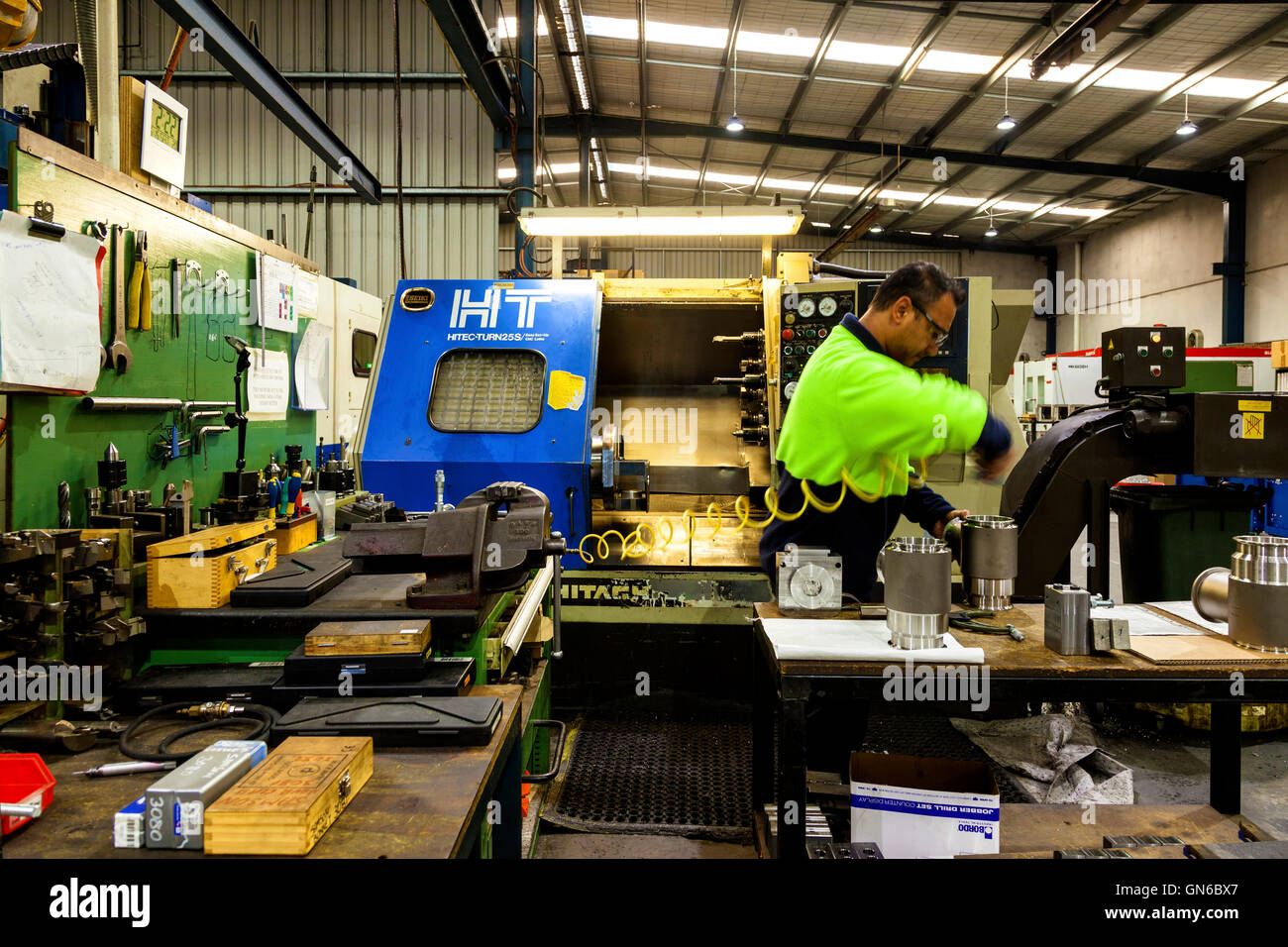 workmen finishing and polishing metal and plastic components ahead of further processing. - Stock Image