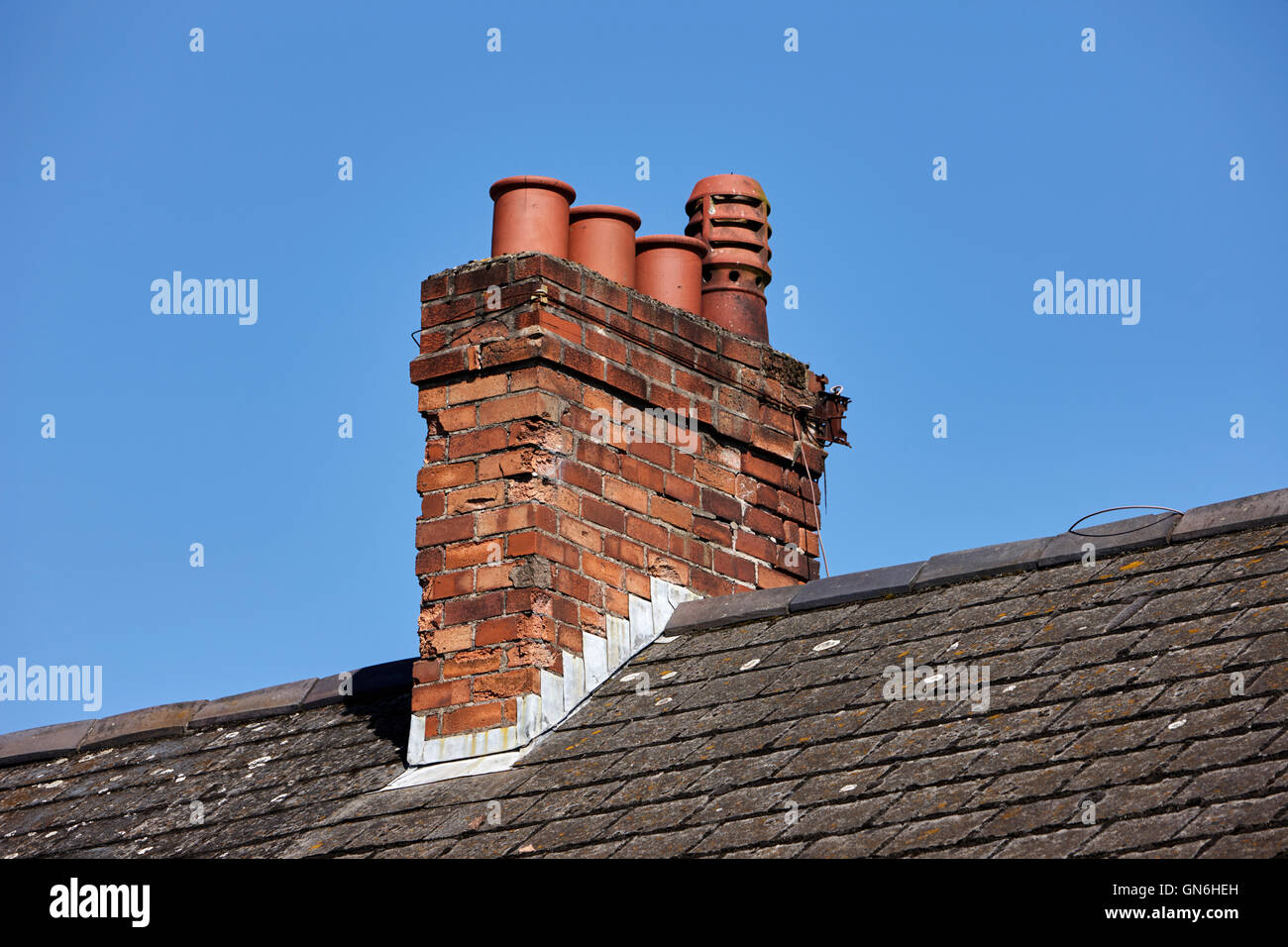 Old Victorian Chimney Stack With Pots On The Roof Of A Row