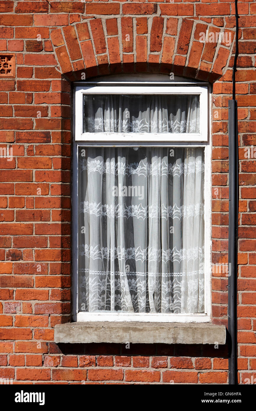 old net curtains hanging in the window of a red brick victorian terraced house - Stock Image