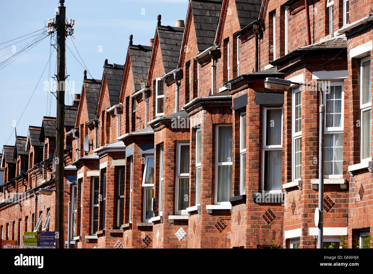 row of upper bay windows in three storey terraced victorian townhouses in a street in south belfast uk - Stock Image