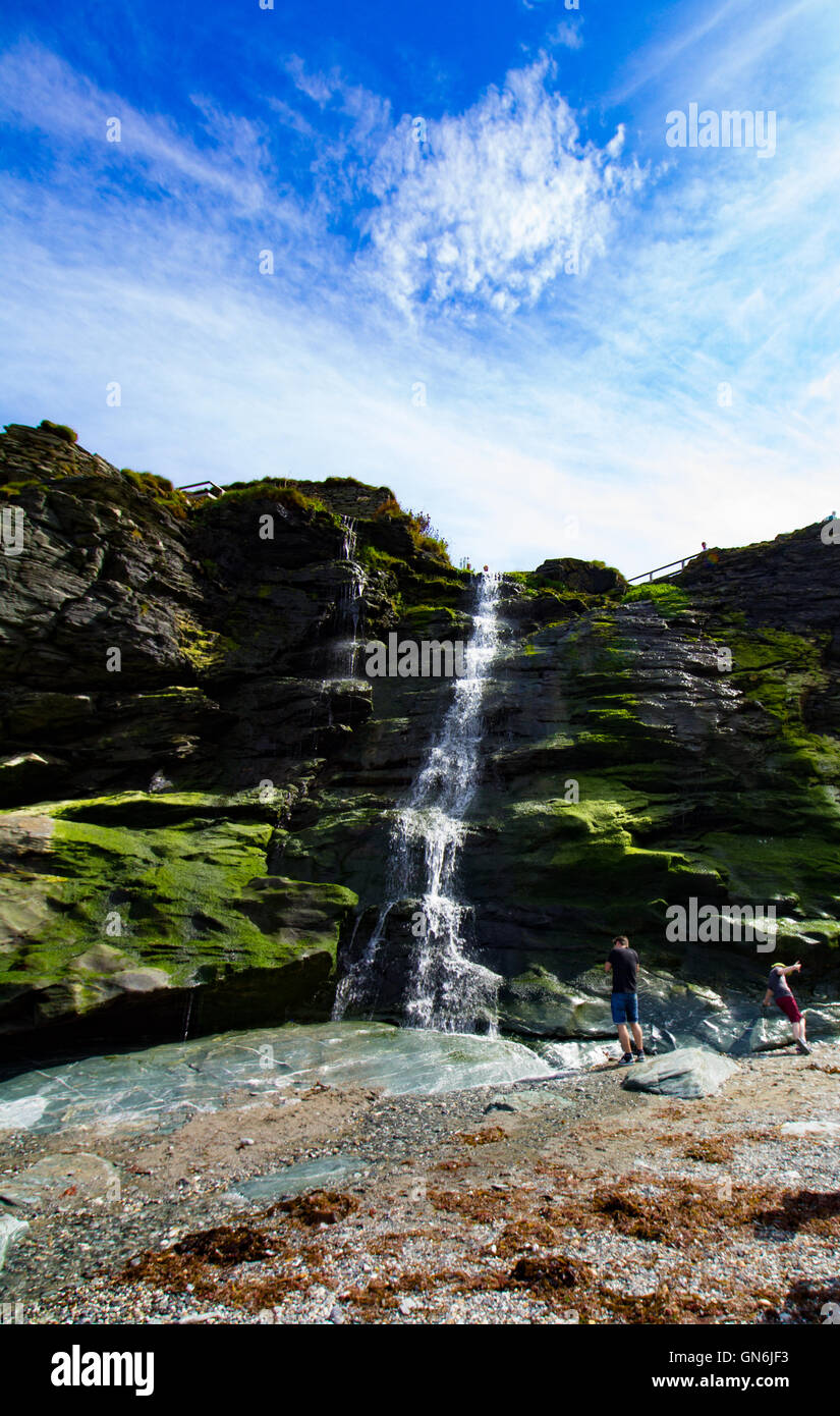 A waterfall flows onto the beach beneath Tintagel Castle in Cornwall, UKStock Photo