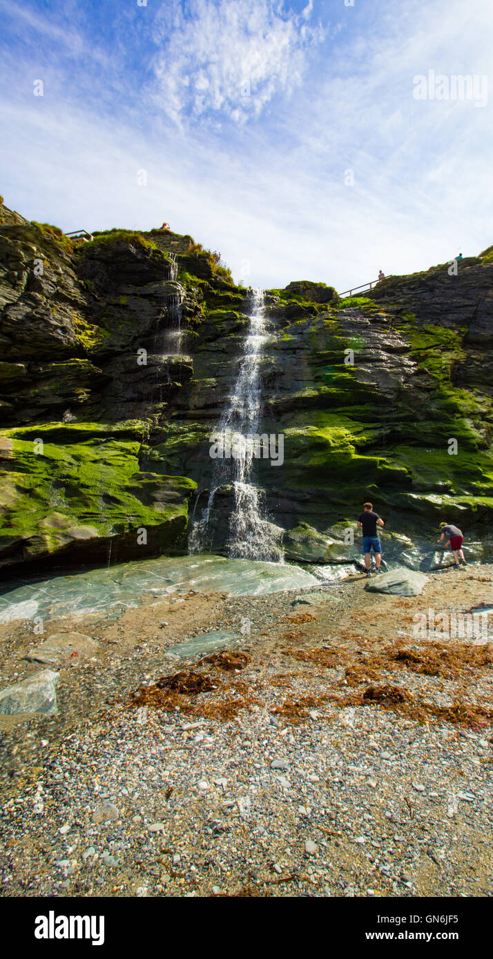A waterfall flows onto the beach beneath Tintagel Castle in Cornwall, UK Stock Photo