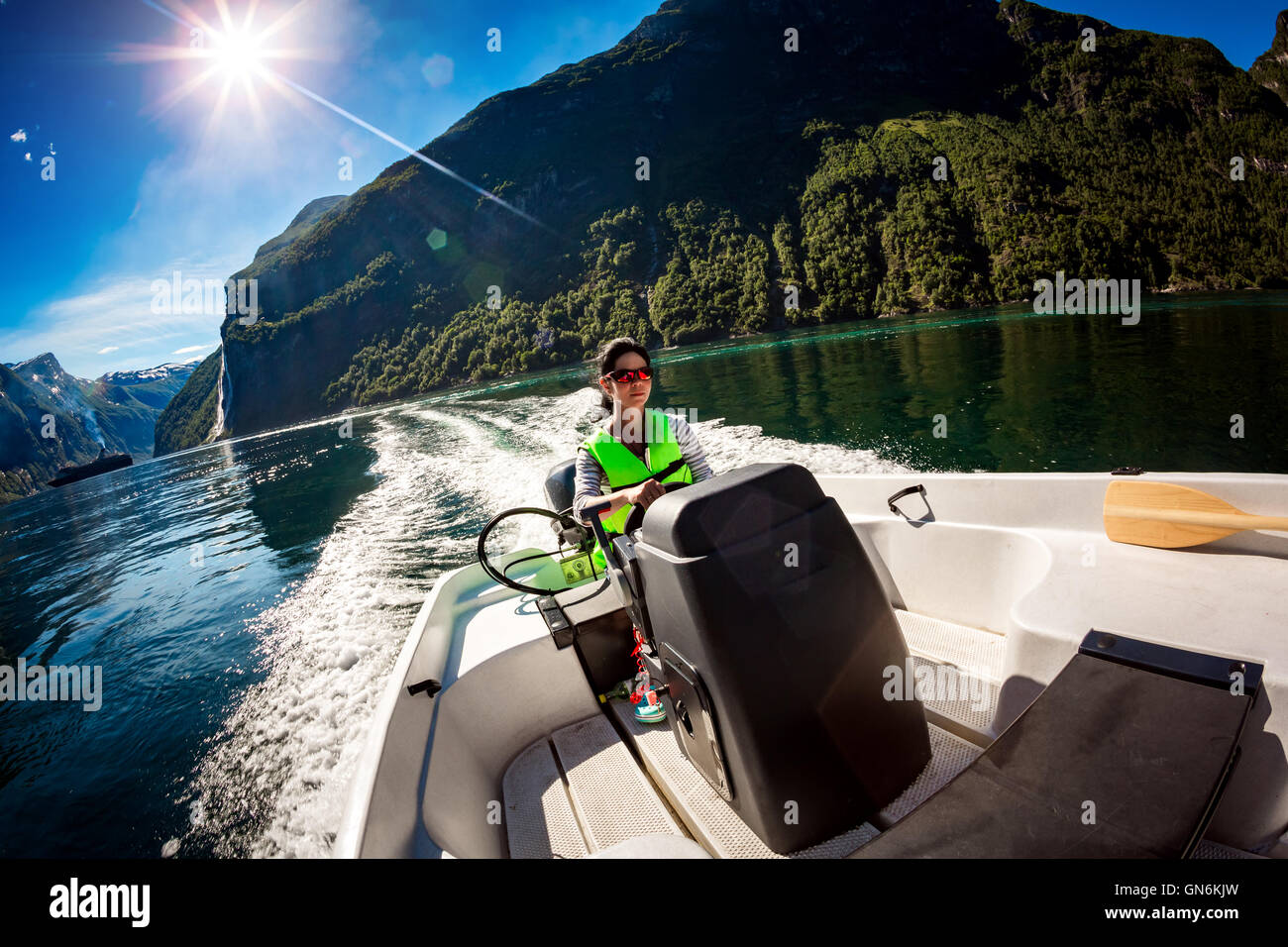 Woman driving a motor boat. Geiranger fjord, Beautiful Nature Norway.Summer vacation. - Stock Image