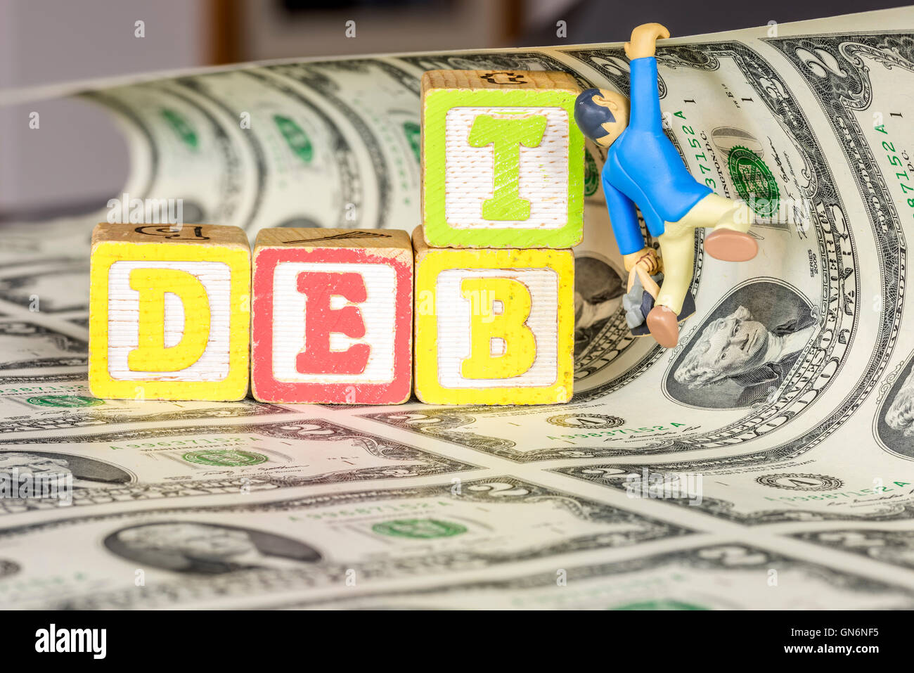 Toy hangs on to money with blocks spelling debt - Stock Image