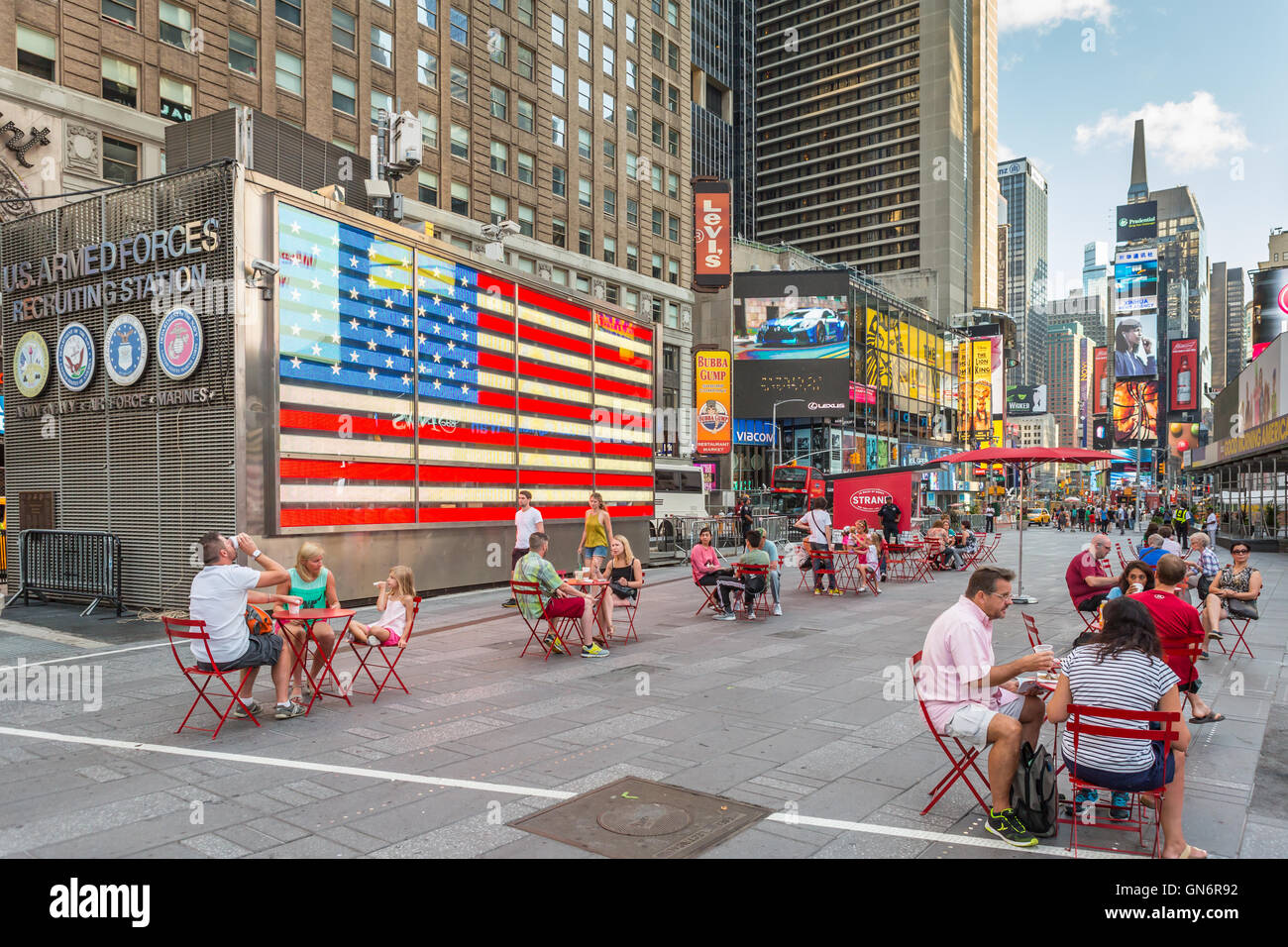 People enjoy the seating in the pedestrian plazas in Times Square  early on a weekend morning in New York City. - Stock Image