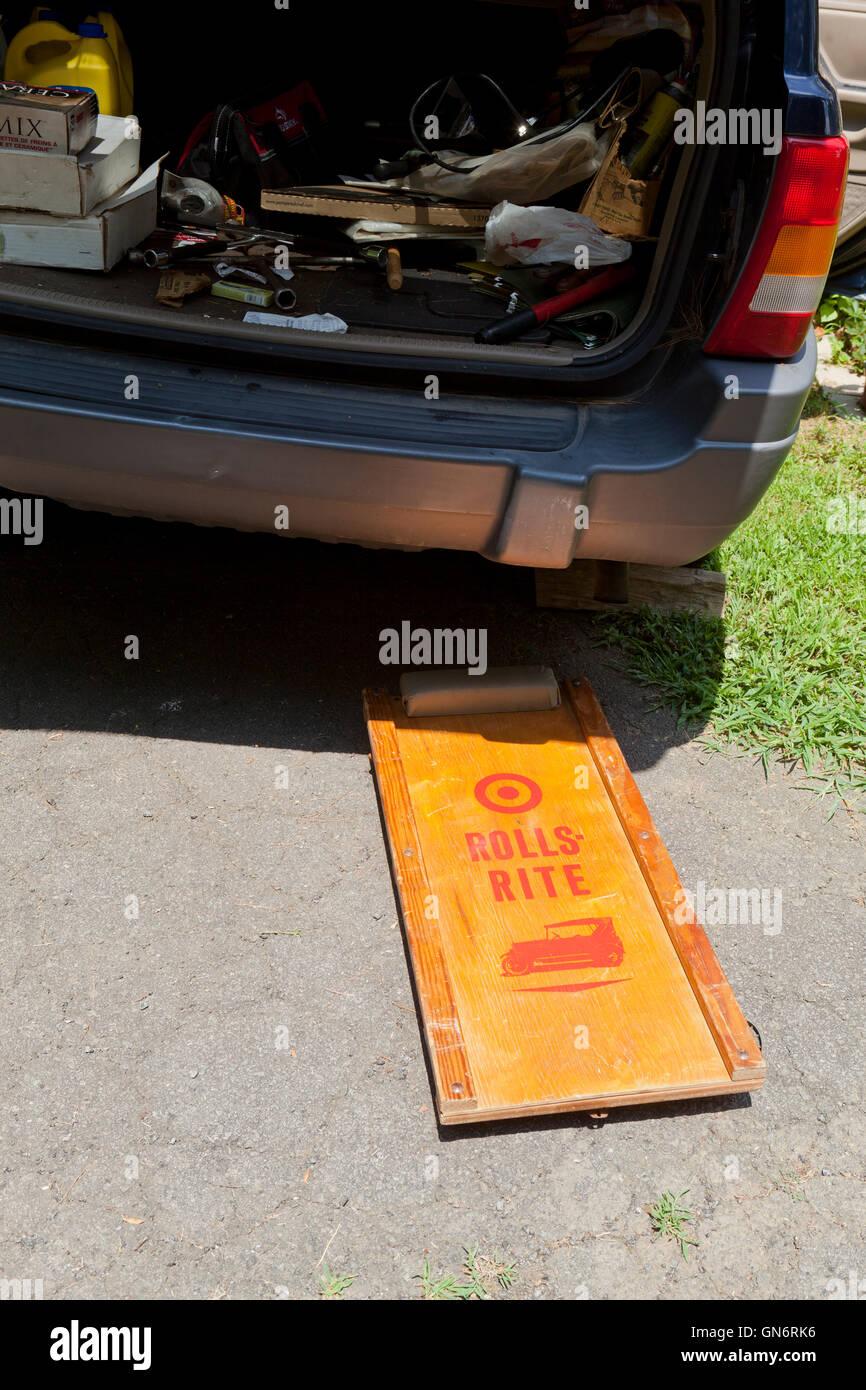 Wooden mechanic's roller creeper under car - USA - Stock Image