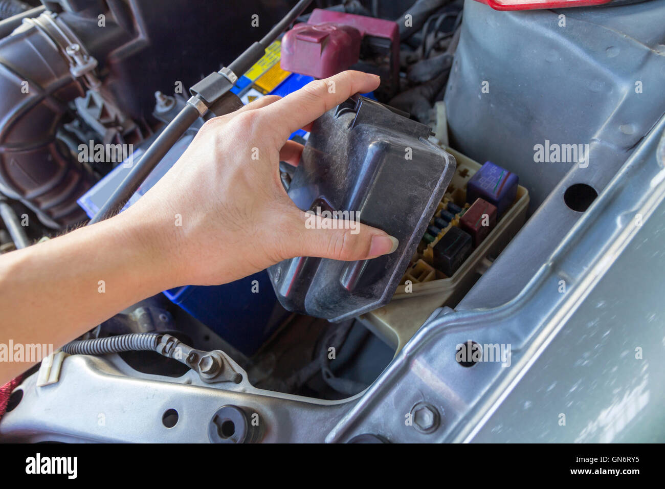 the man opening fuse box of old car - stock image