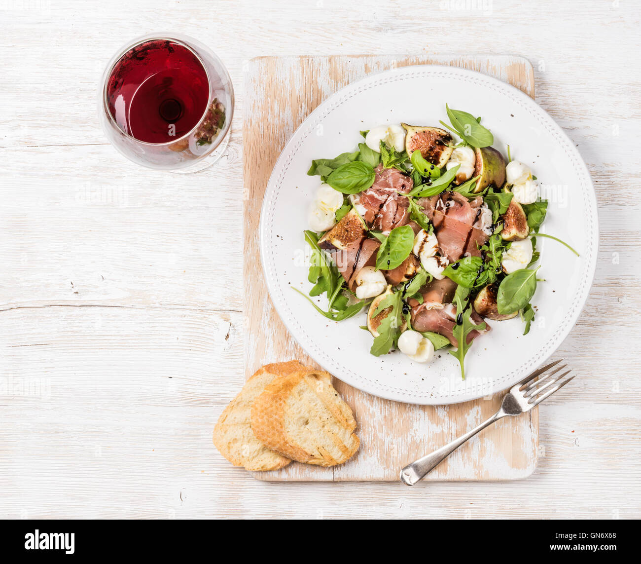 Prosciutto, arugula, figs salad with baguette slices and wine - Stock Image