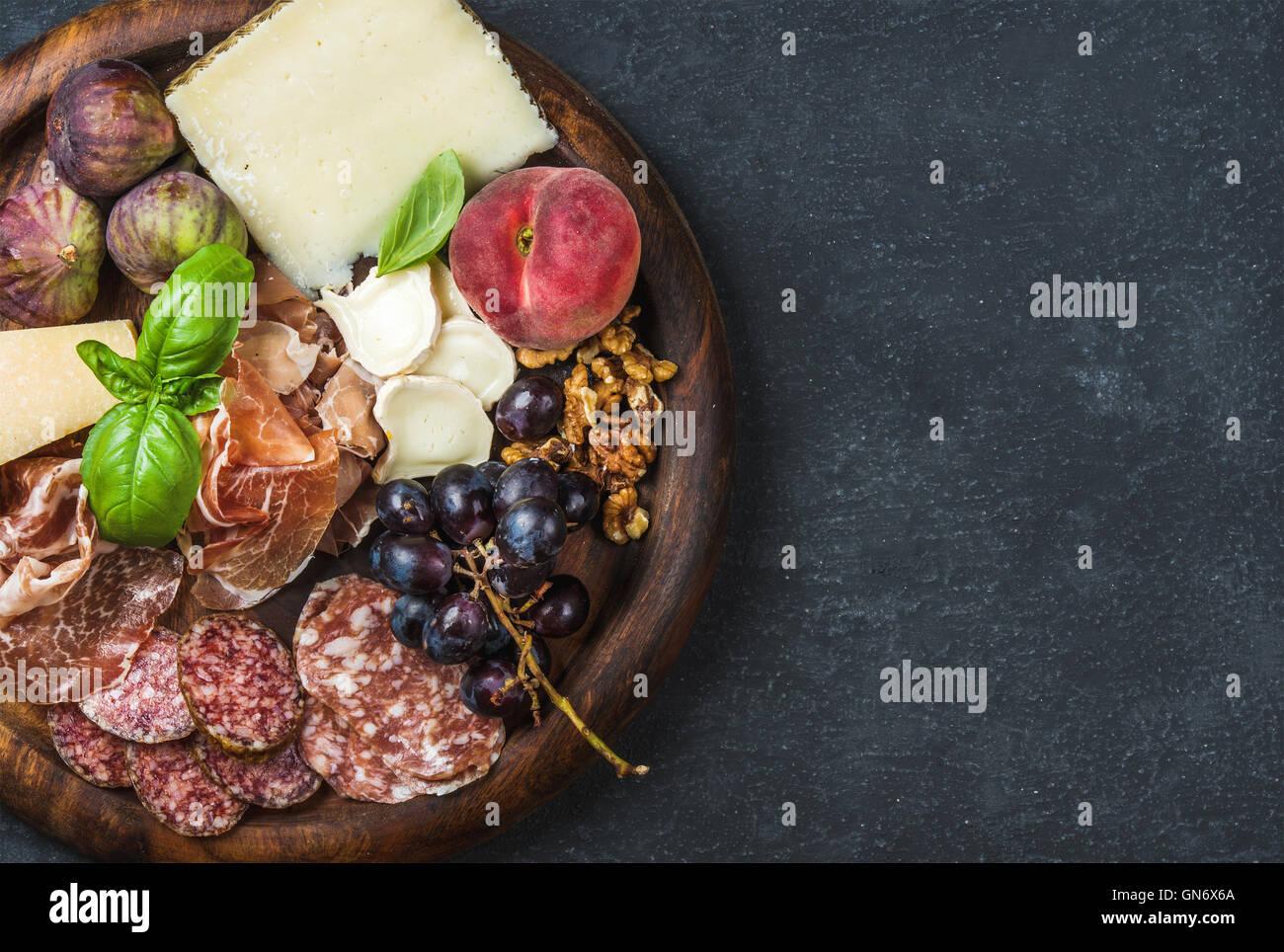 Italian wine snacks variety over dark plywood background, copy space - Stock Image