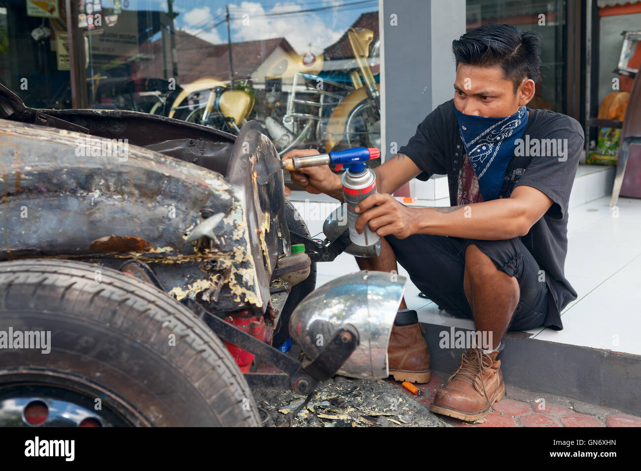 BALI, INDONESIA - MARCH 20: Young Balinese man cleans a body of an old volkswagen beetle during restoring vintage - Stock Image