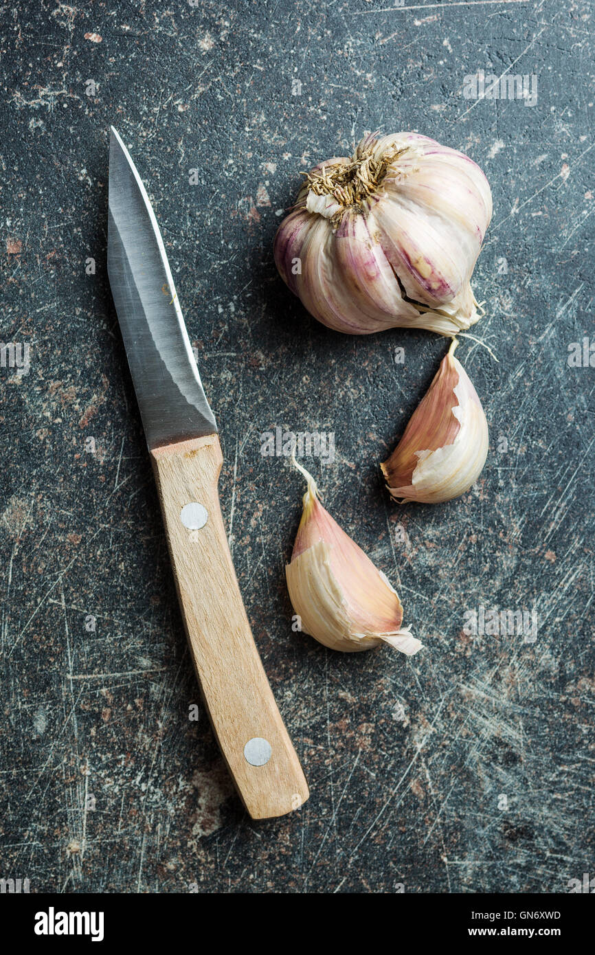 The fresh garlic with knife on kitchen table. - Stock Image