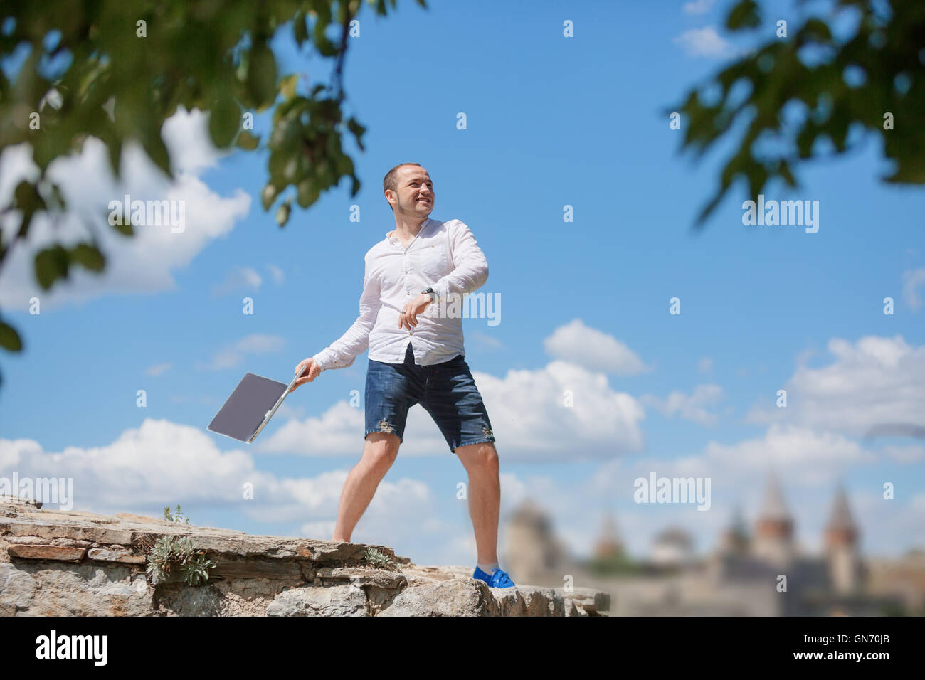 man throws notebook against blue sky - Stock Image