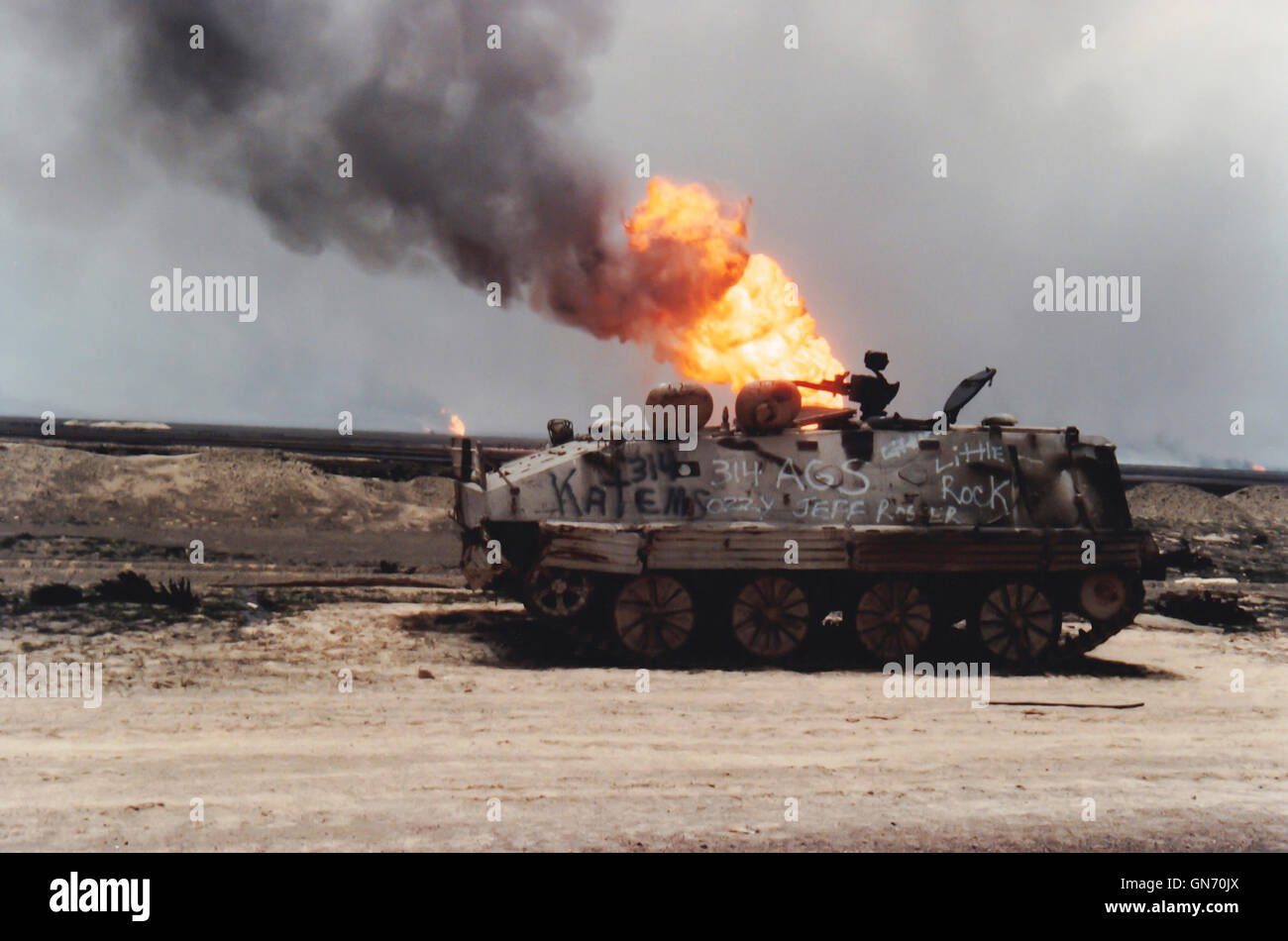 Kuwait City, Kuwait - April 1991 :  Damaged tank on road with burning oil fire from Persian Gulf War. - Stock Image